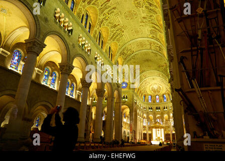 Woman taking photo high arched interior Ste Anne de Beaupre Cathedral Chateau Richer QC - Stock Image