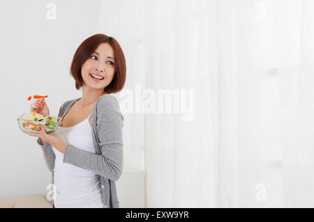 Young woman holding salad and looking away with smile, - Stock Image