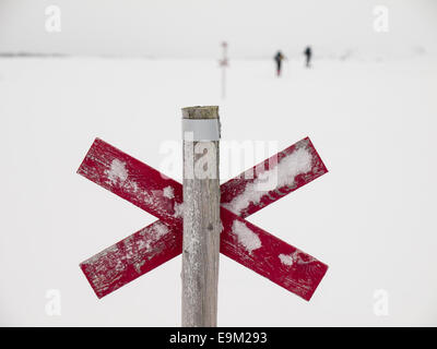 wooden trail marker next to d trail in the Northern Swedish mountain area of Sylarna (sylan) with  skiers out of - Stock Image