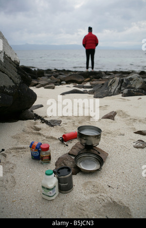 A man looking out to sea whilst camping on the beach at Applecross Wester Ross - Stock Image