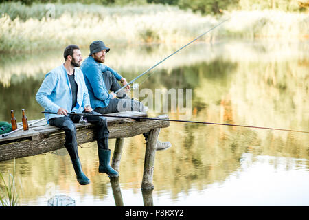 Two male friends dressed in blue shirts fishing together with net and rod sitting on the wooden pier during the morning light on the lake - Stock Image