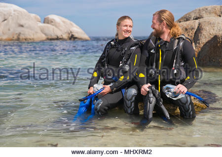 Couple in wetsuits smiling at each other before ocean scuba diving from beach - Stock Image