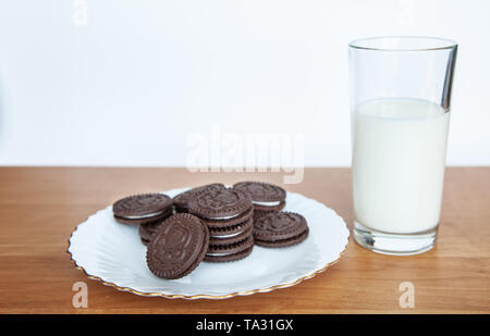 plate with cookies and a glass of milk on the table indoor closeup - Stock Image