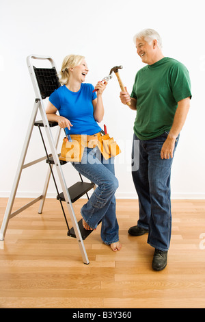 Middle aged couple with household tools next to ladder - Stock Image