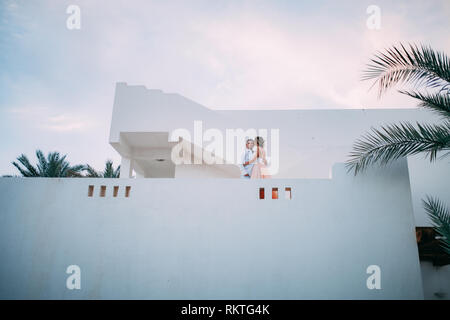 Happy newlyweds stand on terrace of white villa against background of palms branches and sky during the honeymoon in Egypt. - Stock Image