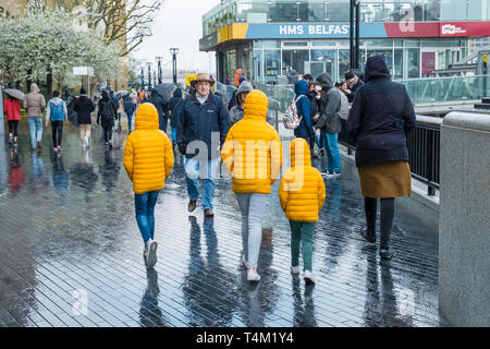 Three children walking along the Southbank in London and wearing matching bright yellow jackets in the rain - Stock Image
