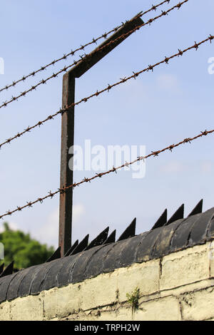 Close up of outdoor high security, barbed wire fence, angle bracket and razor spikes on wall: to deter unauthorized access & for perimeter protection. - Stock Image