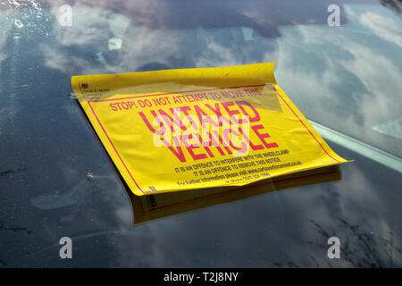 Untaxed vehicle sticker on the windscreen of a car immobilised at the roadside by a yellow DVLA clamp, for non-payment of road tax - Stock Image