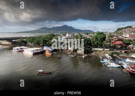 Wooden taxi boat ferry carries passengers across the river in Manado, Sulawesi, Indonesia. Bunaken Island is in the background. - Stock Image