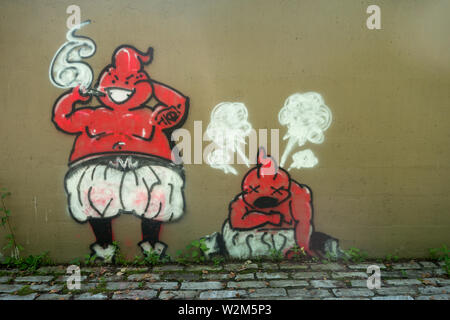 Two strange red creatures painted as graffiti on a cement wall. - Stock Image