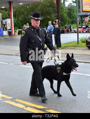 A police officer marching in the 4th of July parade with his K-9 police dog in Speculator, NY USA - Stock Image