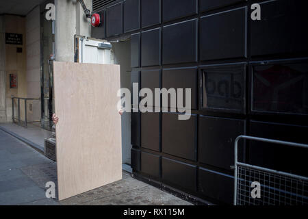 An obscured workman manhandles a wooden board sheeting into a construction site doorway, on 5th March 2019, in London, England. - Stock Image