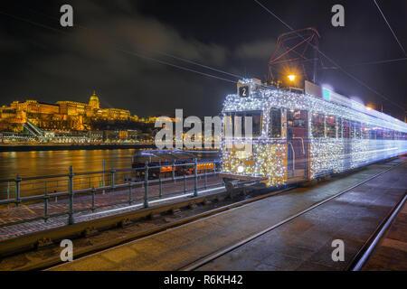 Budapest, Hungary - Festively decorated light tram (fenyvillamos) on the move with Buda Castle Royal Palace at Vigado square by night. Christmas seaso - Stock Image