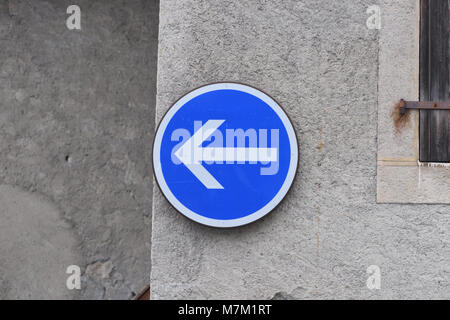 A blue and white traffic direction sign in the form of an arrow on a stone wall. Samoens, Haute Savoie, France. - Stock Image
