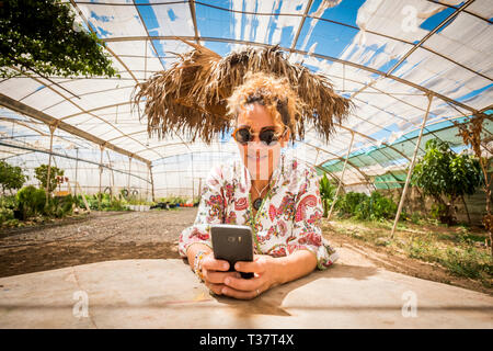 Beautiful cheerful curly blonde young caucasian woman use modern phone typing message or searching on internet in outdoor rural scenic place during su - Stock Image