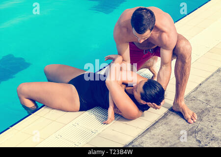 Lifeguard taking woman out of the pool. Toned image. - Stock Image