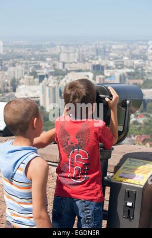 Boys looking at view of Almaty from Kok Tobe mountain, Almaty, Kazakhstan - Stock Image