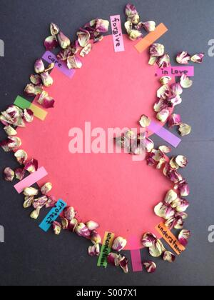 Heart of paper with rose petals and stickers with written words - Stock Image