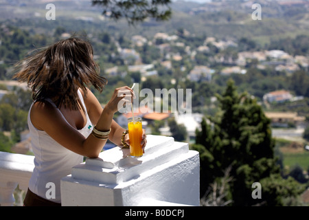 Young woman tourist holding glass of orange juice while enjoying the view from Mijas Pueblo, Costa del Sol, Andalucia, - Stock Image