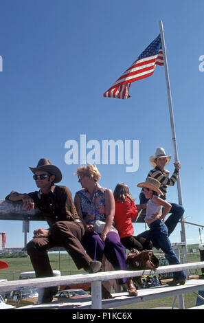 Family at a rodeo stampede event in Stapleton Ohio with son holding up an American flag - Stock Image