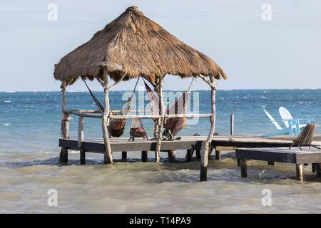 Beach Gazebo and Peaceful Seascape on Belize Caye Caulker Waterfront with Distant Caribbean Sea on the Horizon - Stock Image