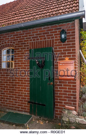 A pair of shoes attached to an old door beside an original-style Deutsche Post box on a brick house. - Stock Image