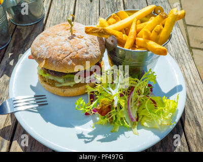 Café  lunch  a prime beef burger  with cheese bacon potato chips and salad - Stock Image