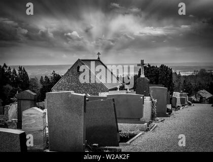 Black and white rendering of graveyards in cemetery and sun rays converging on top of a church cross - Halloween composition with space for names and - Stock Image