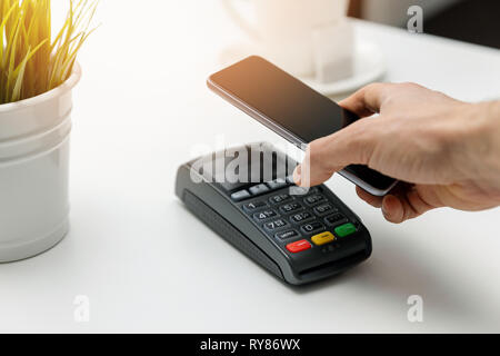 nfc contactless payments - paying bill with phone - Stock Image