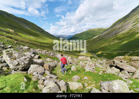 A female hiker walking towards Hartsop and Brock Crags  in the English Lake District, UK. - Stock Image