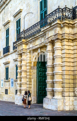 Two young lost women in front of the Grand Master's Palace, the former residence of the Grand Masters of the Knights of St. John - Valletta, Malta. - Stock Image