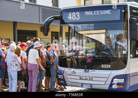 GARDA, LAKE GARDA, ITALY - SEPTEMBER 2018: Crowd of people waiting to get on a bus in the bus station in the town of Garda on Lake Garda. - Stock Image