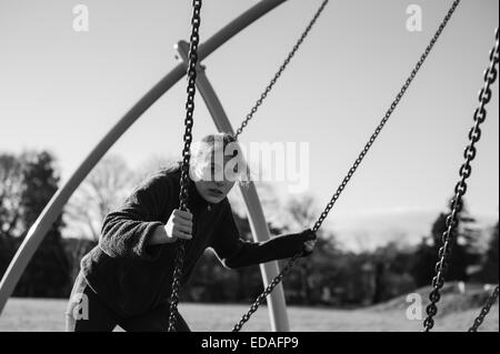 A girl balances on a rope supported by chains in a playground in Daventry Northamptonshire - Stock Image