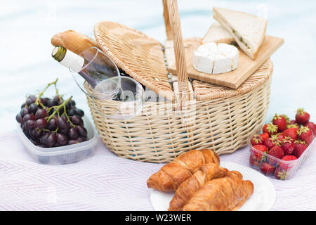 picnic basket, food and wine glasses on blanket - Stock Image