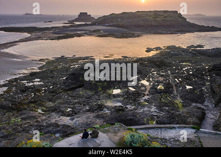 Two younger men sitting on a rock watchig the sunset at St Malo, Brittany, France - Stock Image