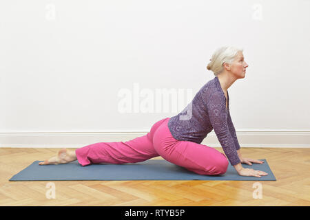 Senior woman with gray hair exercising yoga at home on a mat in front of a white wall, asana pigeon intro - Stock Image