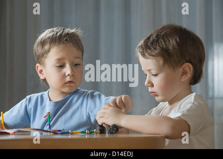 young boys playing with shape game - Stock Image