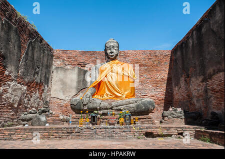 Large stone Buddha statue at the partially restored ruin of Wat Worachet Tharam in the ancient city of Ayutthaya, - Stock Image