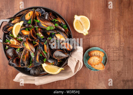 Marinara mussels, moules mariniere, with toasted bread and lemon slices, in a cooking pot, overhead shot on a dark rustic wooden background - Stock Image
