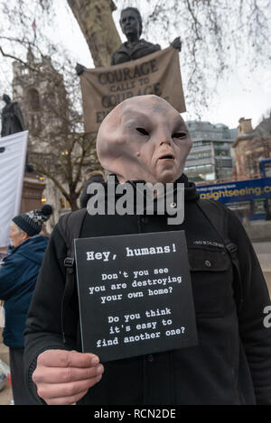 London, UK. 15th January 2019. A 'spirit of a venusian' gives  a warning to Earth Strike UK campaigners in Parliament Square beginning the first of 4 international actions leading to a global General Strike on 27th September 2019, leaving work & school, boycotting non-necessary consumption and protesting in our streets to demand urgent change to halt global mass extinction, the destruction of our world by catastrophic climate change caused by greenhouse gases, mainly from using carbon fuels, coal, oil and gas. Credit: Peter Marshall/Alamy Live News - Stock Image