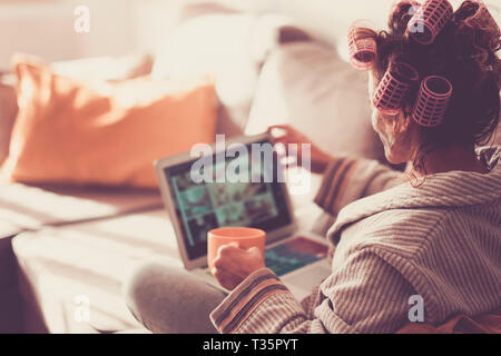 Lady viewed from back using a modern technology laptop at home while have curlers on his curly hair - coloured tones vintage - relaxation at home drin - Stock Image