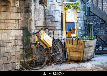 Vintage Bike Chained to the Wall around Beautiful Flowers and Decorative Boxes - Stock Image
