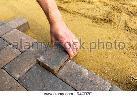 Person laying block paving on to sharp sand - Stock Image