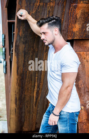 Man in urban setting in front of big metal structure - Stock Image