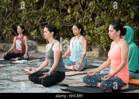 Group of five women meditating while sitting on yoga mats. Yoga retreat Puerto Vallarta - Mismaloya, Mexico - Stock Image
