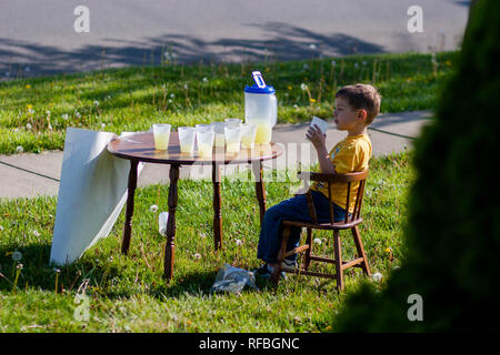 A 5-year old boy sits at a lemonade stand with cups and a pitcher of lemonade. - Stock Image
