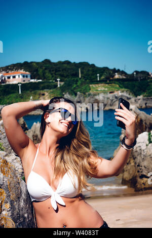 Blond woman with sunglasses using wireless headset and mobile phone. - Stock Image