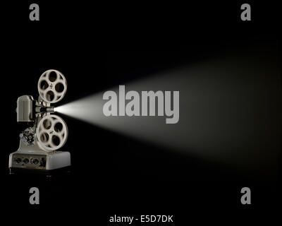 A three quarter angle shot of an old style film projector shot against a dark background - Stock Image