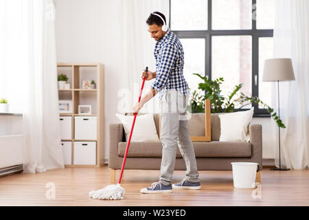 man in headphones with mop cleaning floor at home - Stock Image