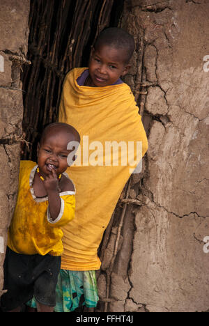 Two Masai Children in the doorway of a mud hut in a village in the Masai Mara, Kenya, Africa - Stock Image